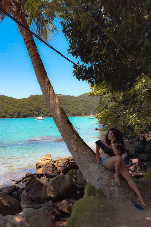 menina observando o mar ao lado de um coqueiro