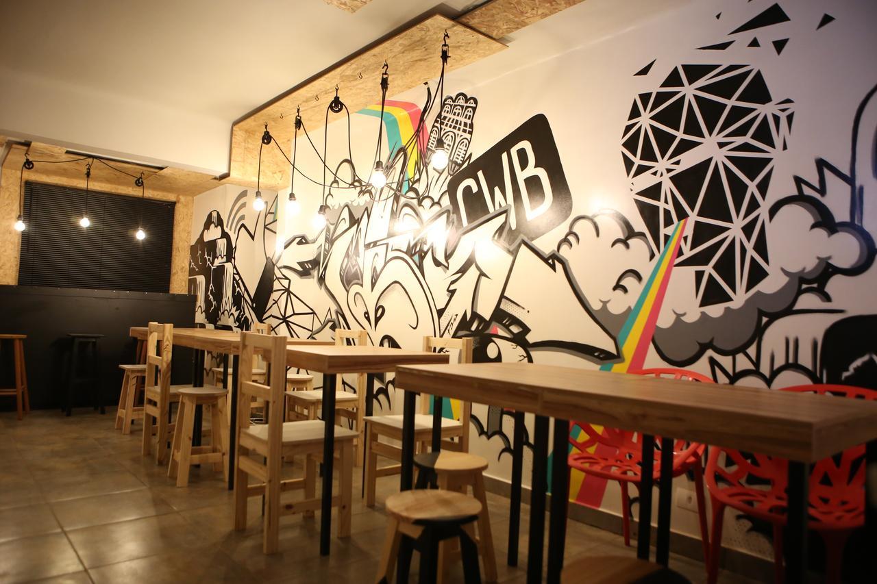 Mesas de madeira com cadeiras, ao fundo parede grafitada no social hostel Curitiba